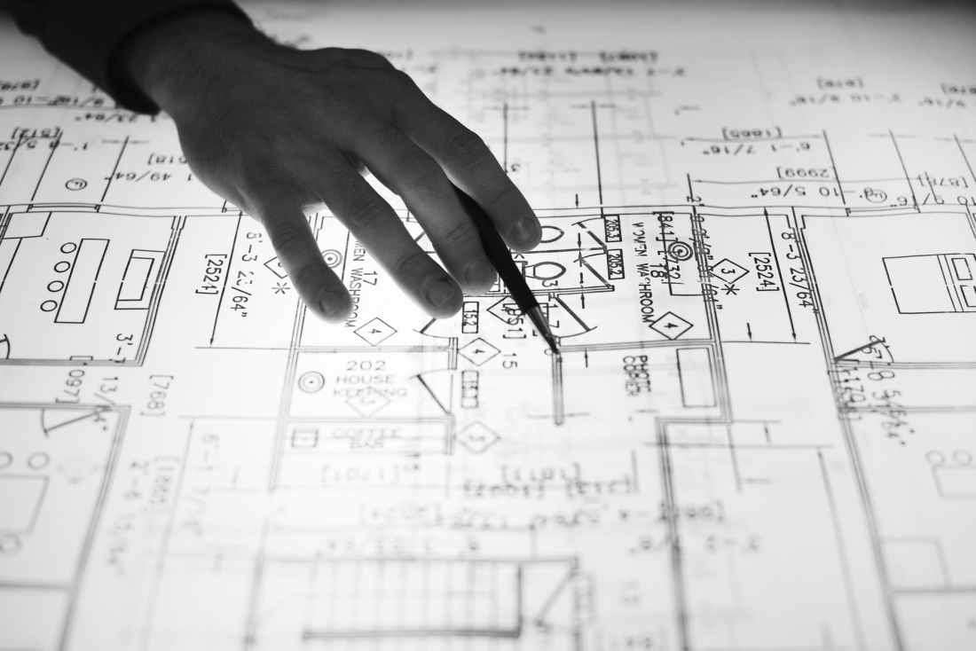 person holding pen point on blueprint